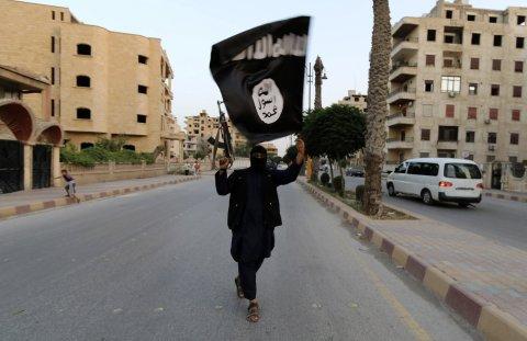 Un membro fedele allo Stato islamico sventola la bandiera nera del jihad in Raqqa